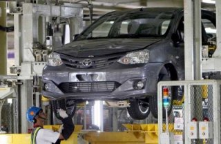 An Indonesian worker inspects a passenger automobile at the Toyota plant in Karawang, western Java, Indonesia. (picture: AAP).