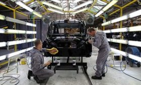 Workers making a black colored taxi inside factory regarding the London Taxi business factory.